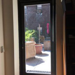 Single medium stile dark bronze aluminum/glass door with glass unit frame
